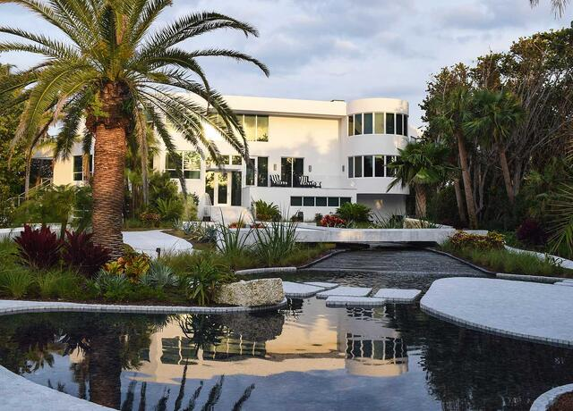 Backyard with water, palmtrees and mansion